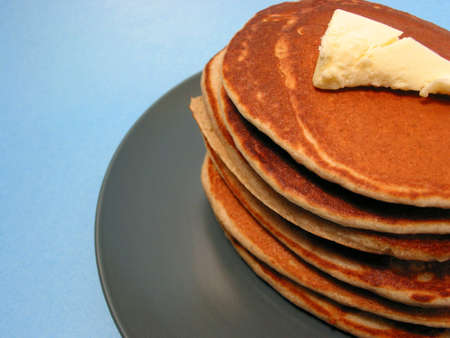 Stack of pancakes on a plate with melting butter, blue background, space for copy
