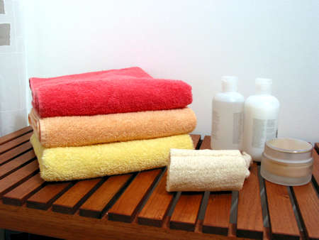 Spa or bathroom accessories: stack of colorful towels, loofah sponge, lotions, shampoos, creams