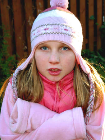 shiver: A young girl wearing a winter hat, shivering in cold weather