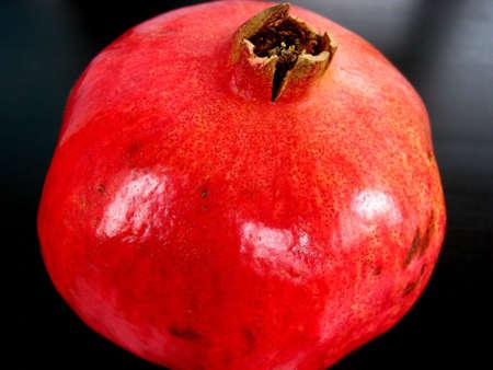 Bright red pomegranate on dark background