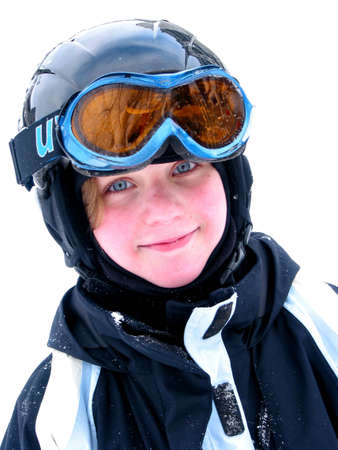 Cute young girl wearing ski helmet and goggles smiles after a day of skiing photo