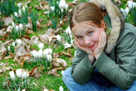 Beautiful young girl sitting among blooming spring flowers photo