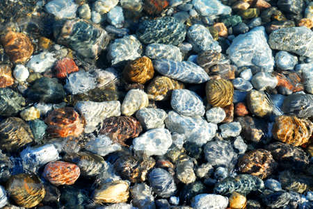 Colorful rounded pebble in clear water with sun reflections photo