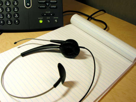 ip: Headset and notepad on the office desk with IP phone in the background