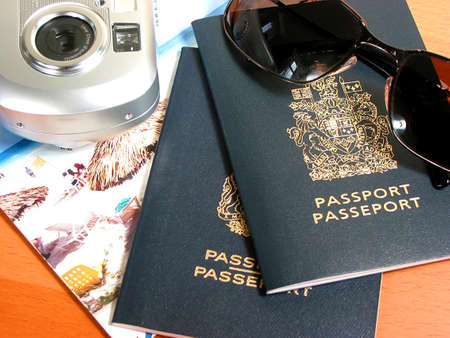 Travel necessities: sunglasses, passports, camera Фото со стока