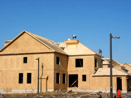Construction of a new house with workers on the roof