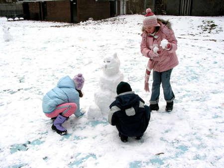 trois enfants: Trois enfants faisant un snowman Banque d'images