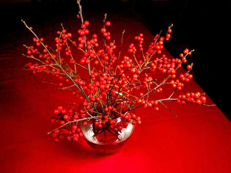 Red berry tree branches in a clear glass vase on red tablecloth photo