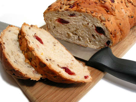 Artisan pumkin seed and cranberry bread on a cutting board with a bread knife, white background photo