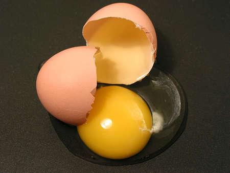 Broken egg on a non-stick pan, closeup photo