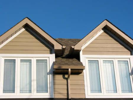 dormer: Detalle de una nueva casa en un brillante cielo azul de fondo  Foto de archivo