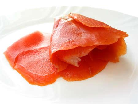 Smoked salmon on a white plate Фото со стока
