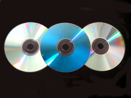 Three compact disks on black background