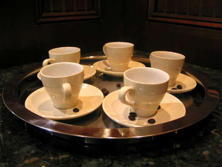 White coffee cups with coffee beans on a tray on a granite countertop