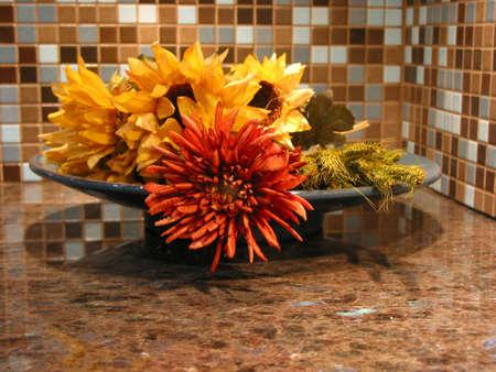 モダンなキッチンで花崗岩のカウンター トップ上にボウルに人工花
