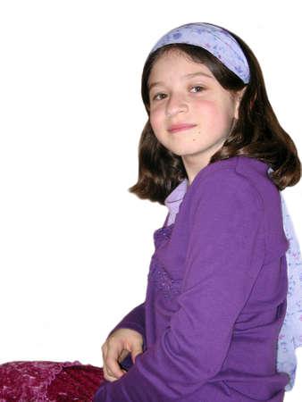Jong meisje met paarse hairband zitten geïsoleerd op witte achtergrond