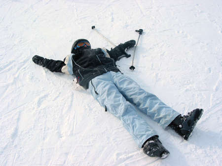 Young girl resting on snow after a day of downhill skiing photo