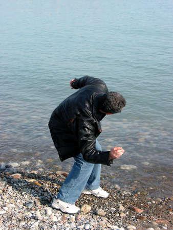Een man gooide steentjes in het water op de wal