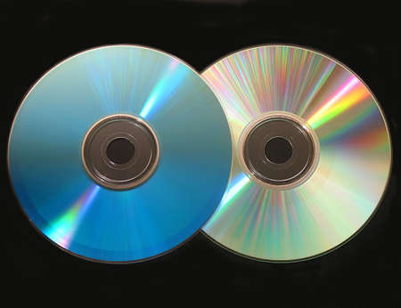 Two colorful compact disks on black background