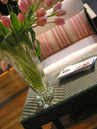 Vase of pink tulips on a coffee table in from of a chair in a living room Stock Photo