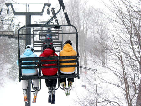 Skiers on chairlift at ski resort photo