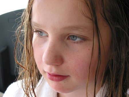 Portrait of a young girl in a bathrobe with wet hair