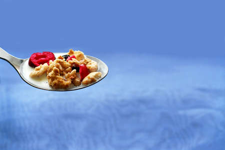 steel  milk: Spoon of cereal on blue background Stock Photo