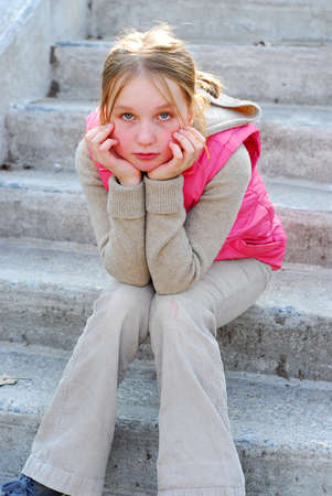 Young girl sitting on concrete stairs Stock Photo