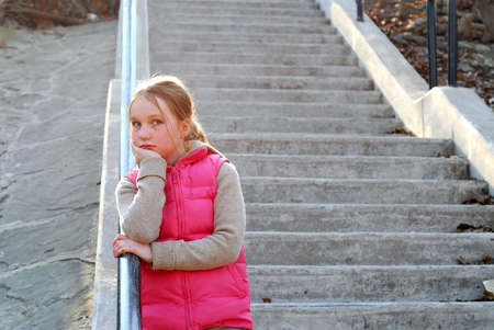 Young girl standing on concrete stairway photo