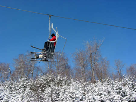 View from below on downhill ski chairlift with snowy firs and bright blue sky in the background Stock Photo - 375166