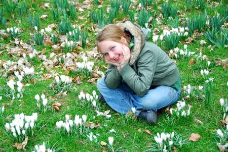 Young girl sitting among blooming white crocuses photo