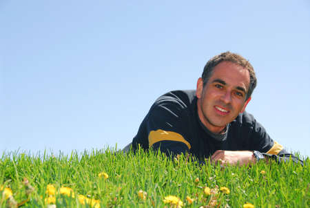 Smiling man lying on grass on background of blue sky Stock Photo - 387567