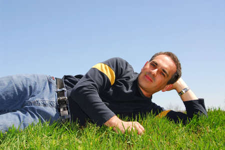Smiling man lying on grass on background of blue sky Stock Photo - 387562