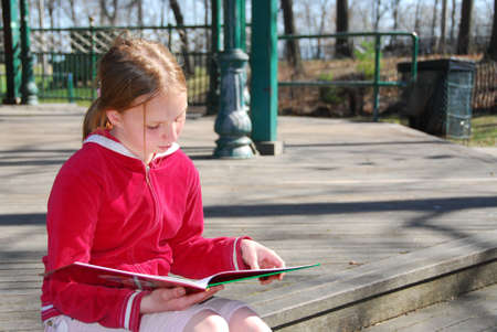 Young girl reading a book outside Imagens