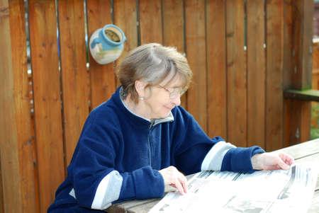 Senior woman reading newspaper on a deck Stock Photo - 387547