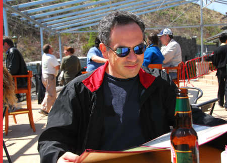 Man sitting on a restaurant patio reading menu