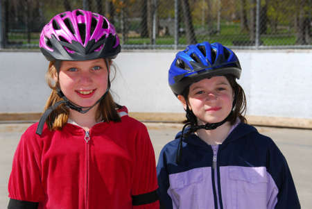 rollerblading: Two happy girls rollerblading in helmets