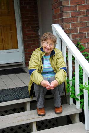 Senior woman sitting on a porch Stock Photo - 408412