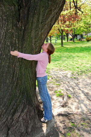 protect: Young girl standing near ancient big tree. Protect environment concept.