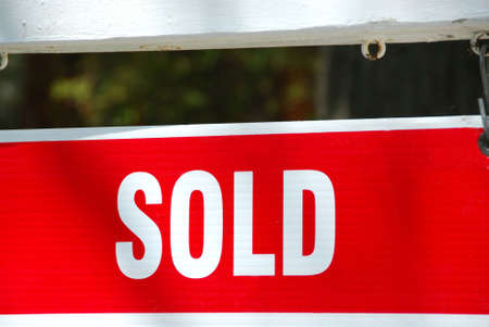 Sold sign near a house, closeup photo