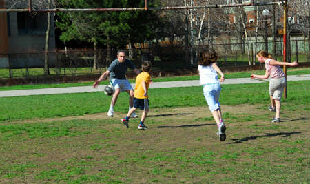 schoolyard: Family playing soccer in a schoolyard