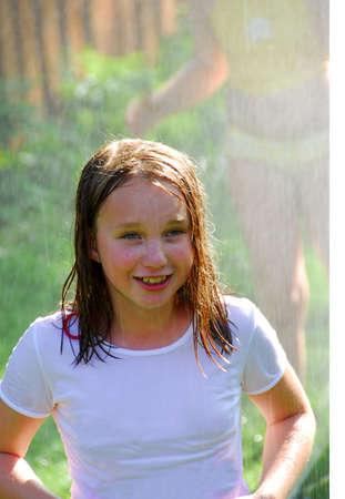 Girls running though a sprinkler photo