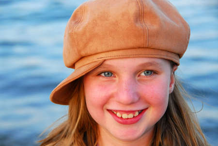 Cute preteen girl in a brown hat on blue water backround Stock Photo - 419051