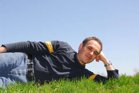 Man lying outside on a grass on a background of cloudless blue sky photo