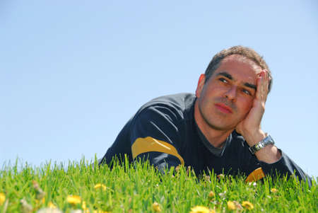 Man lying on a grass on a background of blue sky with concerned expression Stock Photo - 419075