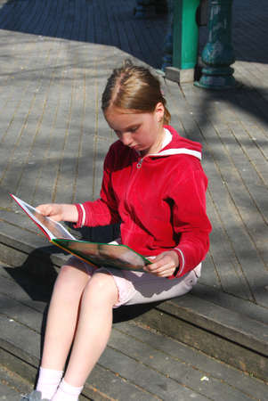 Young girl reading outside photo