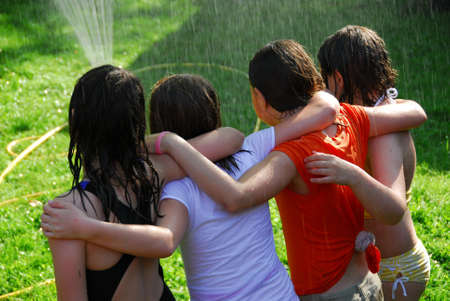 Group of preteen girls having fun outside running through sprinkler