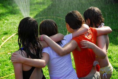 Group of preteen girls having fun outside running through sprinkler photo