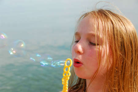 Young girl blowing soap bubbles Stock Photo - 422476