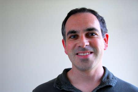 uncluttered: Portrait of a smiling man on plain background